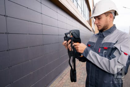 Employee Garant Expert conducts an energy audit of the facade of the building