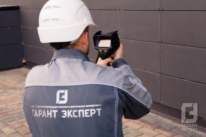 Employee Garant Expert conducts energy building